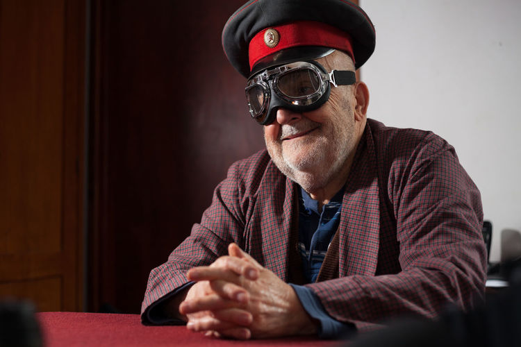funny old man with pilot goggles and cap Aged Bearded Cap Casual Clothing Close-up Comic Funny Goggles Grandfather Grimace Grimacing Hands Headshot Indoors  Joking Leisure Pensioner Pilot Glasses Portrait Retired Retirement Senior Adult Senior Men Sitting Veteran
