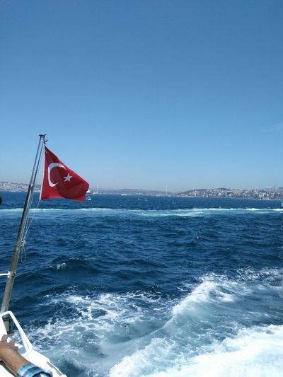 Red flag on sea against clear blue sky