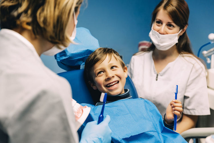 Cheerful patient looking at dentist in operating room