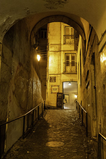Empty alley amidst illuminated buildings at night