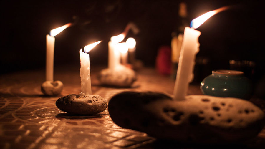 Illuminated candles on stones at night