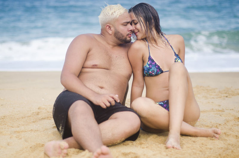 Two People Beach Couple - Relationship Land Togetherness Love Sea Heterosexual Couple Sitting Shirtless Water Bonding Adult Emotion Sand Positive Emotion Men Women Young Couple Beautiful Woman