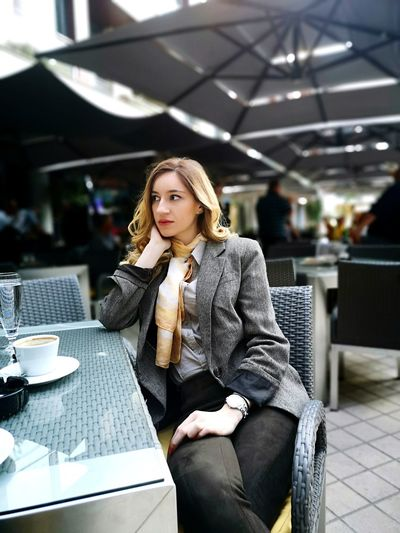Woman looking away while sitting at table in sidewalk cafe