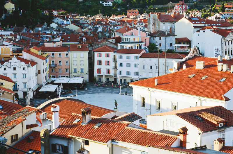 Red roofs of old town piran with main church against the sunrise sky, adriatic sea. slovenia
