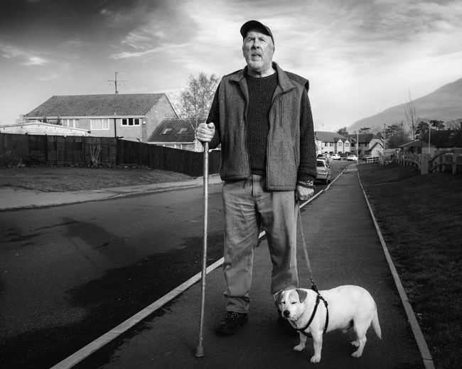 Man standing with dog on sidewalk against sky