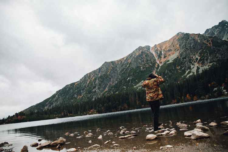 Rear view of person standing on rock against sky