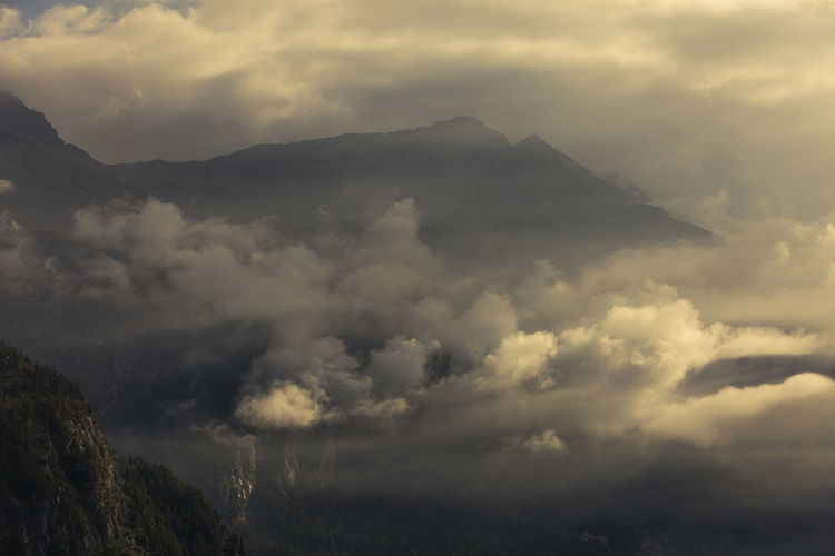 Sunrise light on clouds in Italian alps Cloud - Sky Sky Mountain Scenics - Nature Beauty In Nature Nature No People Environment Tranquil Scene Tranquility Outdoors Non-urban Scene Day Overcast Storm Cloudscape Low Angle View Dramatic Sky Mountain Range Mountain Peak Ominous