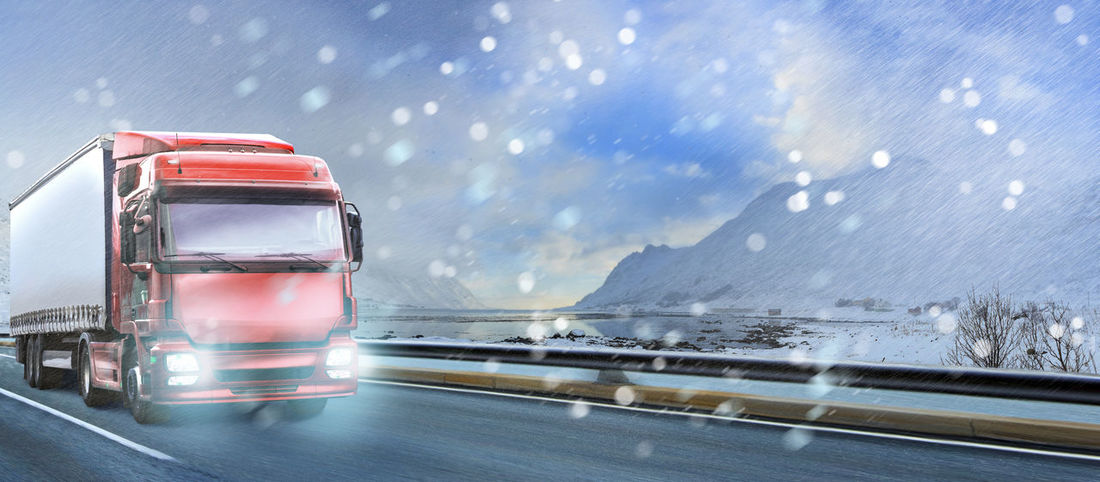 a truck on the road at stormy weather, symbolic picture for cargo and transportation companies Blurred Motion Business, Car, Cargo, Driving, Freight, Landscape, Loading, Lorry, Motorway, Moving, Ocean, Road, Road, Sea, Traffic, Trailer, Transport, Transportation, Travel, Truck, Vehicle Cold Temperature Day Motion Nature No People Outdoors Road Sky Snow Snowing Transportation Water Weather Winter
