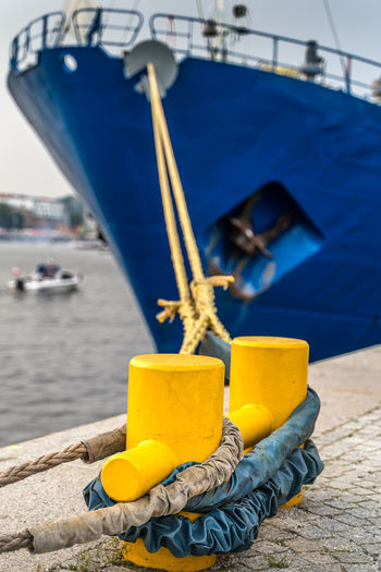 Close-up of yellow moored on pier