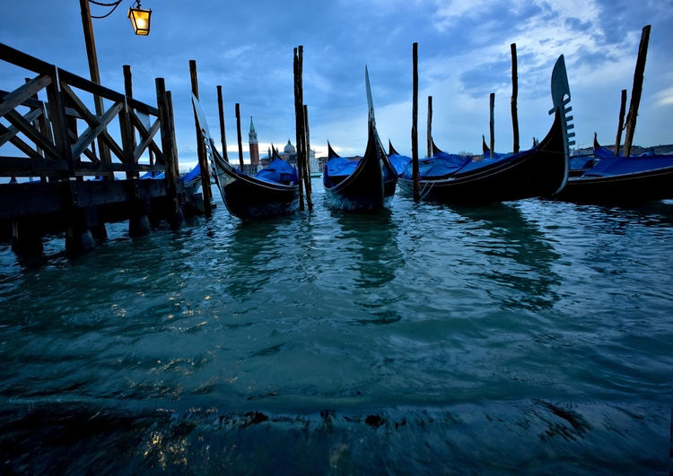 Low angle view of gondolas moored at grand canal against cloudy sky