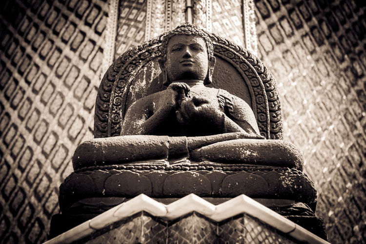 Black and white picture of the Stone Buddha statue at the Wat Phra Kaew Palace, also known as the Emerald Buddha Temple. Bangkok, Thailand. Architecture Bangkok Buddha Thai Thailand Wat Phra Kaew Architecture Art And Craft Buddhism Carving Human Representation Idol Landmark Low Angle View Male Likeness Place Of Worship Religion Representation Royal Palace Sculpture Spirituality Statue Travel Destinations Wall