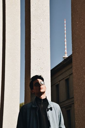 Portrait of young man standing against building