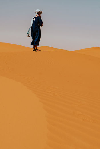 Full length man standing on sand dune in desert against sky