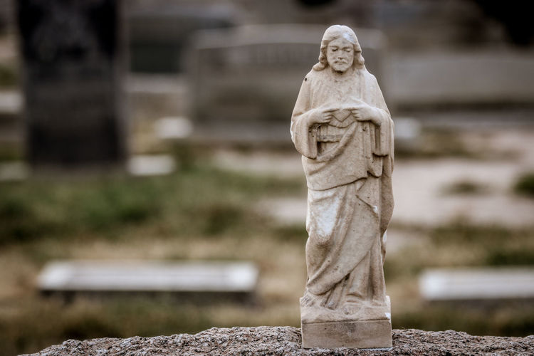 Statue Sculpture Art And Craft Representation Solid Human Representation Grave Cemetery Religion Stone Material Sadness No People Spirituality Tombstone Stone Day Craft Male Likeness Creativity Outdoors Angel