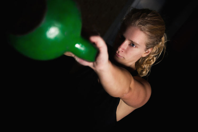 Young Woman Lifting Kettlebell Against Black Background