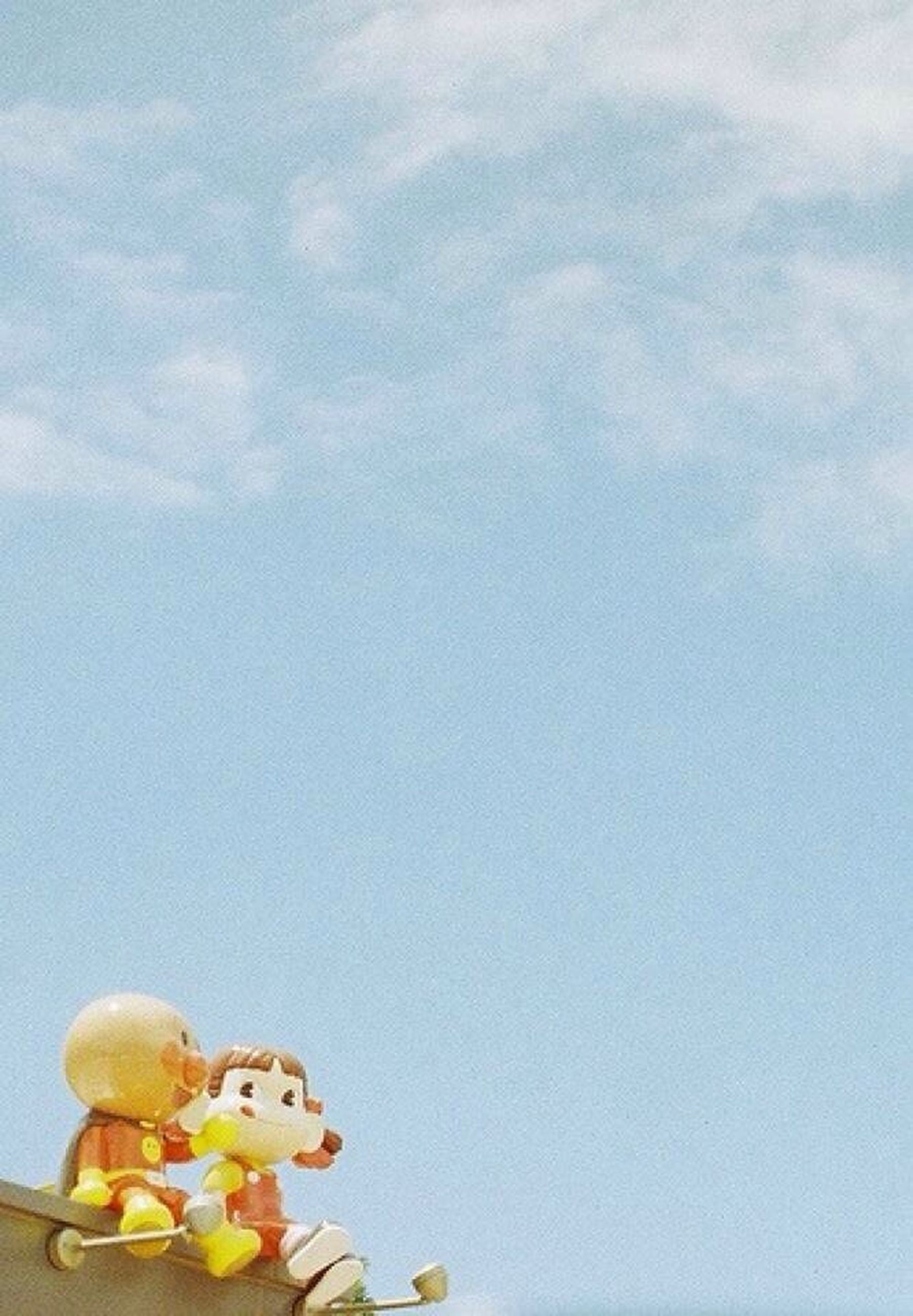 sky, low angle view, copy space, multi colored, yellow, toy, no people, day, variation, outdoors, blue, childhood, still life, cloud - sky, nature, large group of objects, art and craft, side by side, creativity, wall - building feature