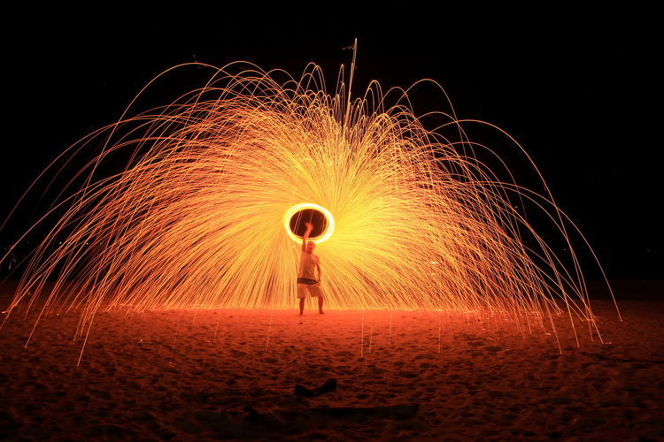Full Length Of Man Spinning Illuminated Wire Wool At Night