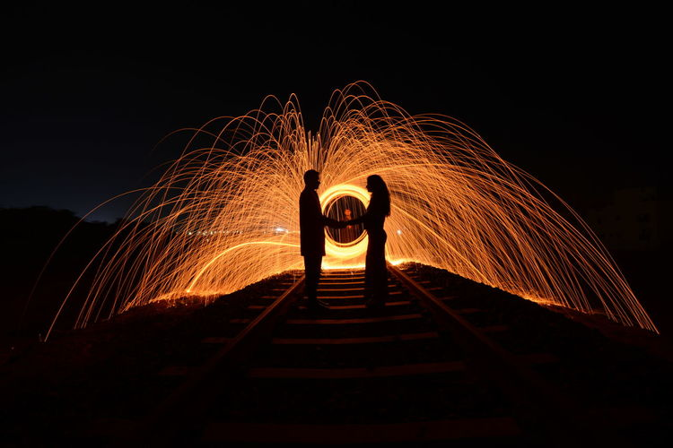 Silhouette Couple Standing By Illuminated Wire Wool Against Sky At Night