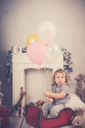 Portrait of cute girl with balloons at home