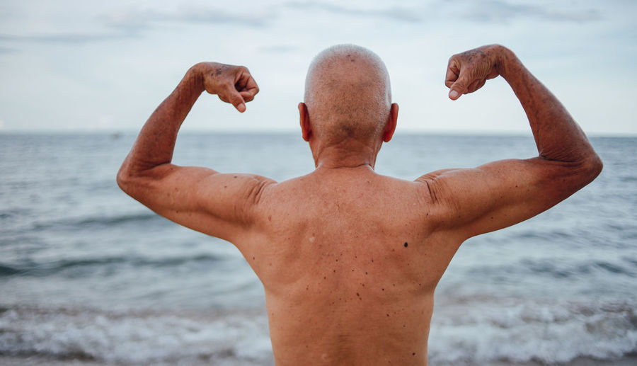 Rear view of shirtless senior man flexing muscles while standing at beach