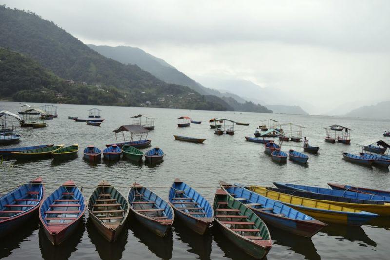 Rowboats moored in phewa lake against sky at pokhara