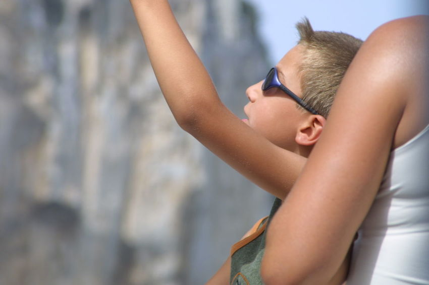 Young boy looking up at cliffs - Capri, Italy Boys Capri, Italy Childhood Close-up Day Elementary Age Focus On Foreground Leisure Activity Lifestyles One Boy Only One Person Outdoors People Real People Tourist Boat Trip