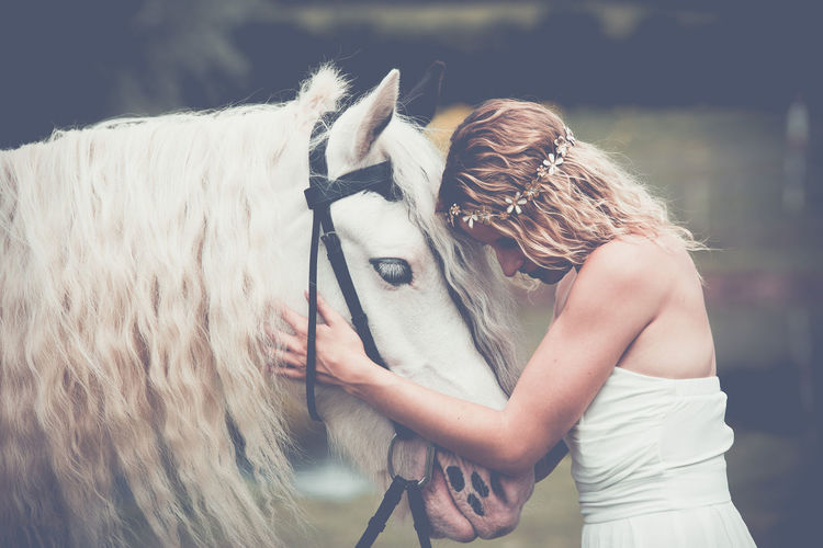 Young woman holding white horse