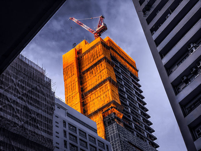 Low angle view of construction buildings against sky in city