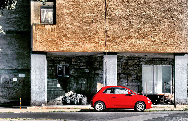 Red car on street against building