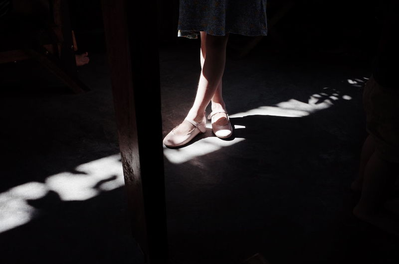 Low Section Of Girl Wearing Shoes While Standing On Floor In Darkroom