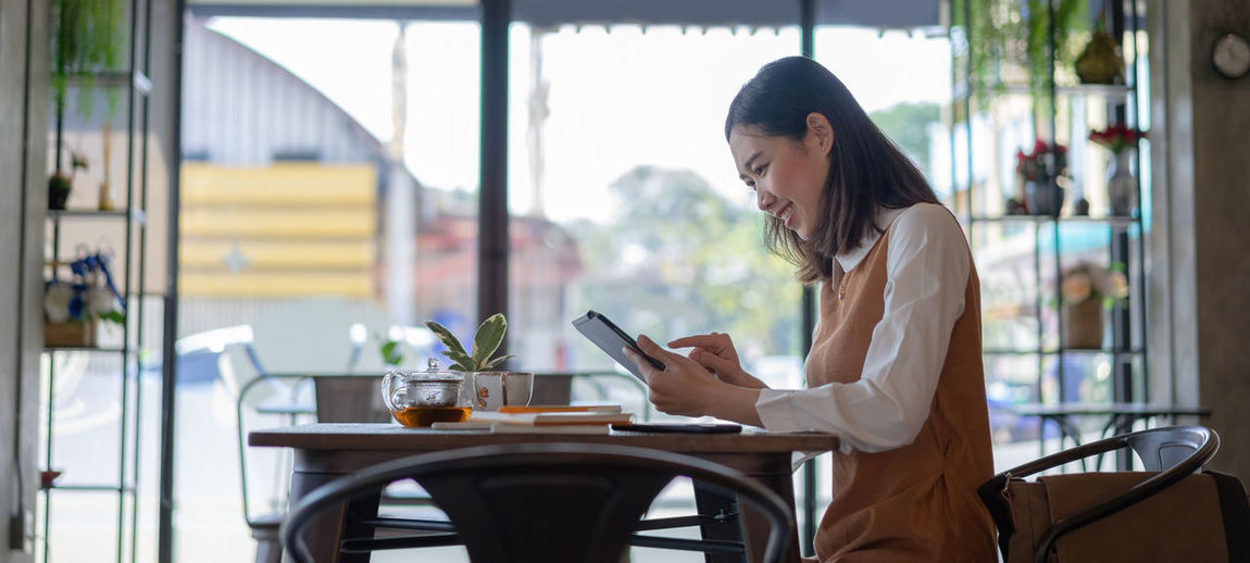 Woman sitting on table in restaurant