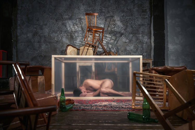 Naked mid adult man sleeping in container at home