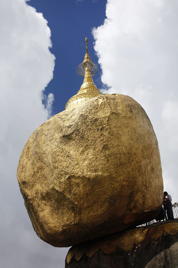 Kyaiktiyo Pagoda Myanmar Outdoors Beauty In Nature Art And Craft Human Representation Rock - Object Rock Low Angle View Gold Colored Solid Day Built Structure Place Of Worship Architecture Nature Spirituality Belief Religion Cloud - Sky Sky Kyaiktiyo Pagoda