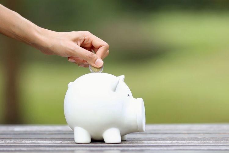 Close-Up Of Hand Putting Coin In Piggy Bank On Table