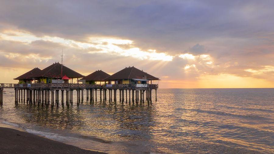 Stilt house on sea against sky during sunset