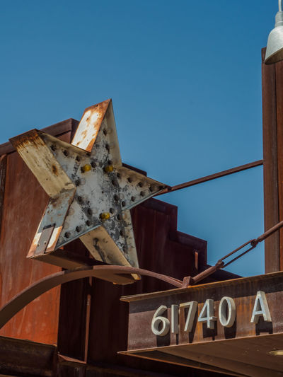 Rusty old star signage on storefront Rust Sign Architecture Blue Building Exterior Built Structure Clear Sky Day Low Angle View No People Outdoors Sky Star Store