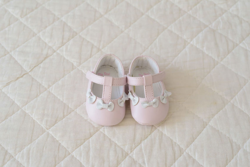 Tiny baby shoes for christening day Baby Bows Celebration Babygirl Babyhood Celebration Event Christening Day Close-up Indoors  No People Pair Pattern Pink Color Sandal Shoe Simplicity Slipper  Still Life White Color