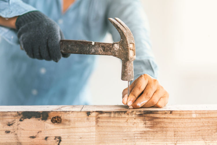 Midsection of man hammering nail on wood