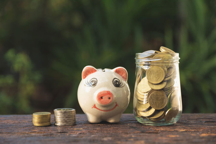 Close-up of coins by piggy bank and jar on table