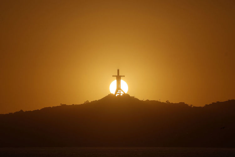 Sunset over the Third Millennium Cross in the city of Coquimbo on October 20, 2017. Photo: Pablo Vera Lisperguer Chile Coquimbo Cross Beauty In Nature Day Men Nature One Man Only One Person Orange Color Outdoors People Scenics Silhouette Sky Sun Sunset Third Millenium Cross Tranquility Water