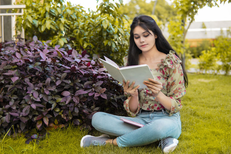 Young woman using mobile phone while sitting on plant