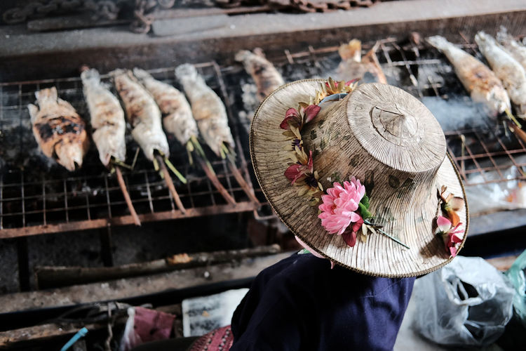 Rear view of woman wearing hat while standing by barbecue grill