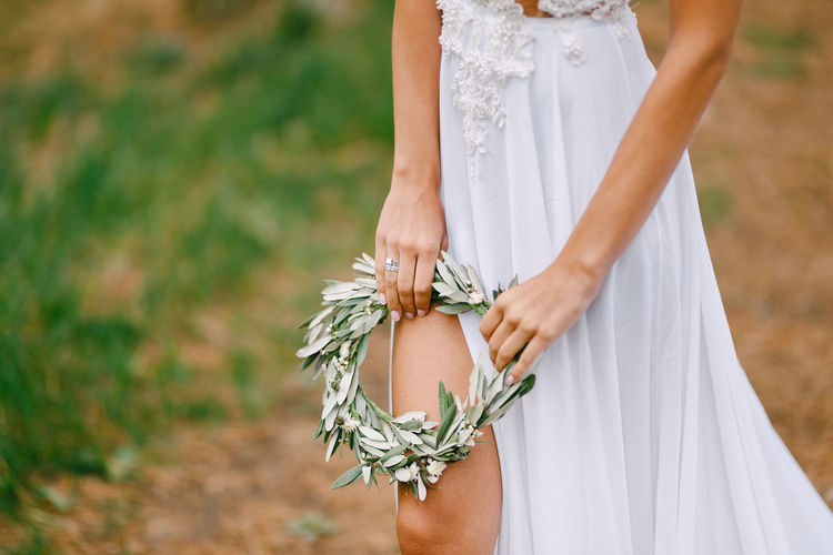 Midsection of woman standing while holding tiara