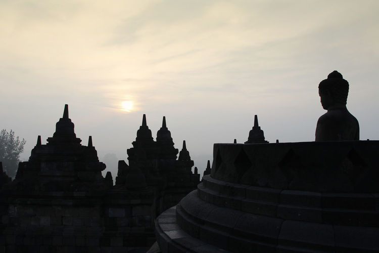 Silhouette Borobudur Temple with the Buddha statue during sunrise, Yogyakarta, Indonesia Borobudur Temple Yogyakarta Ancient Civilization Architecture Belief Buddhism Building Building Exterior Built Structure Dawn History Nature No People Place Of Worship Religion Sky Spirituality Sunrise The Past Tourism Travel Destinations