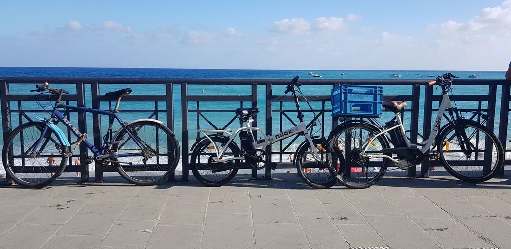 Bicycles on railing against sea