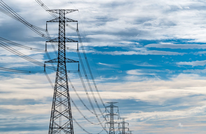 High voltage electric pylon and electrical wire with blue sky and white clouds. electricity pole.