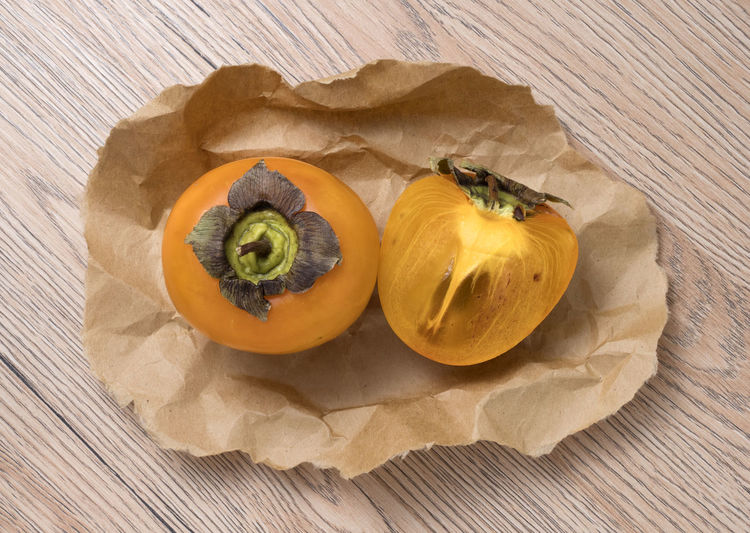 Delicious ripe persimmon fruit on wooden background. Sweet; Orange; Fresh; Nutrition; Fruit; Diet; Persimmon; Delicious; Vegetarian; Food; Vitamin; Ripe; Asian; Healthy; Tropical; Ingredient; Juicy; Dessert; Tasty; Background; Raw; Nature; Natural; Chinese; Nutritious; Exotic; Eat; Edible; Color; Freshness; Food And Drink Food Healthy Eating Freshness Wellbeing Still Life Fruit Table Indoors  No People Wood - Material High Angle View Close-up Persimmon Cross Section Directly Above Vegetable Yellow Orange Color Paper Vegetarian Food