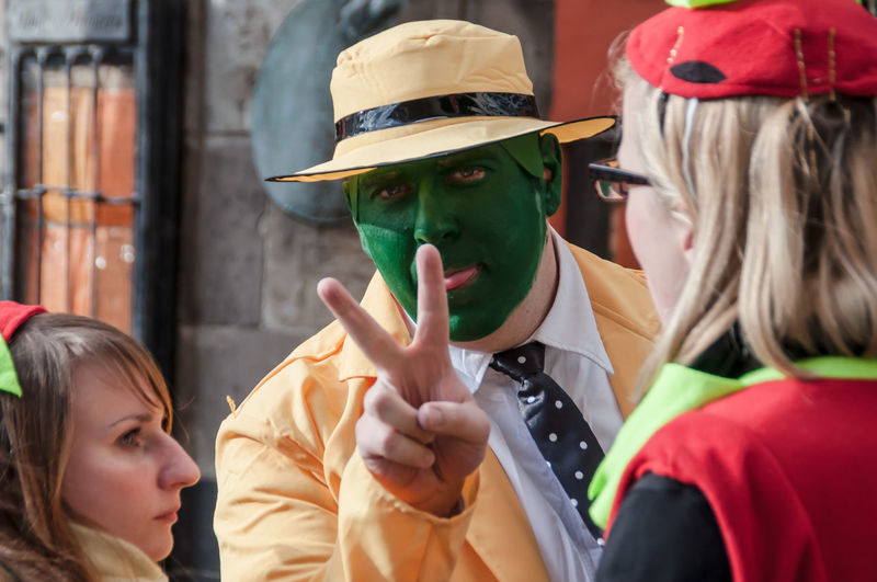 """Cologne, Germany - March 14th 2014: A man wears the costume from the movie """"The Mask"""", a yellow suit with a yellow hat and green face Carnival Celebration Cologne Disguise Event Man Suit Celebration Costume Costuming Dress Up Film Roll Green Face Green Make-up Joy Loonies Makes Nonsense Nonsense Outdoors Reveller Reversal Roleplay Street Carnival The Mask Yellow"""