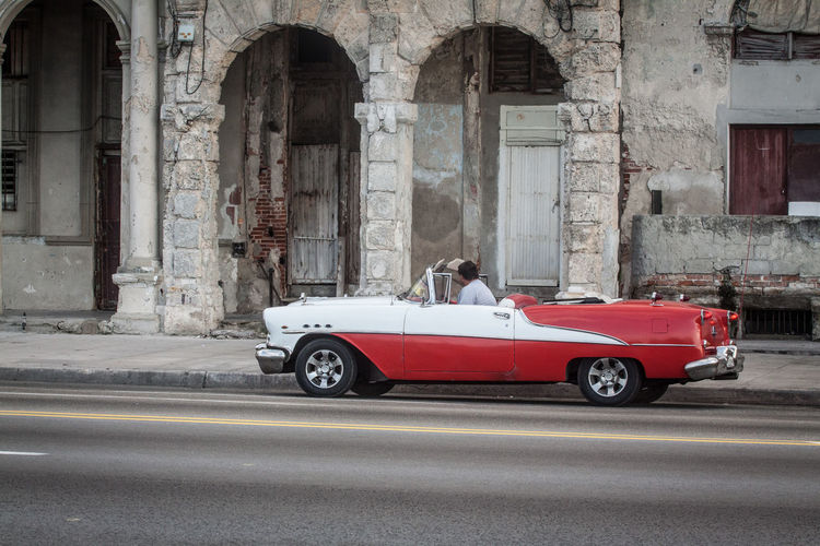 Man In Vintage Car On Road By Old Building