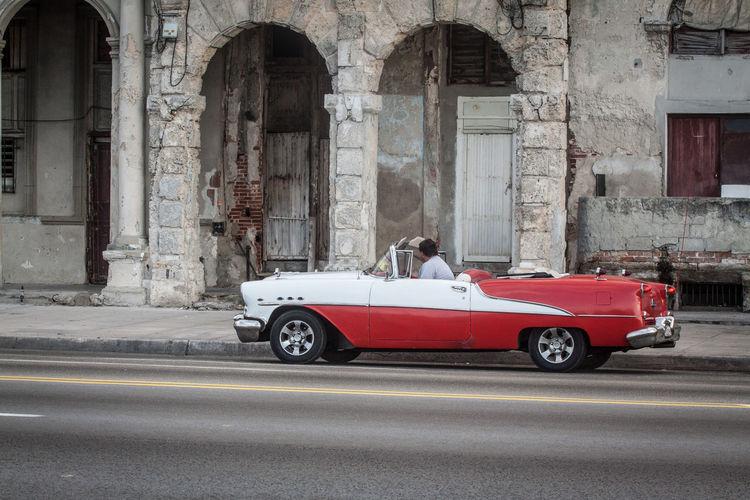 Man in vintage car on road by old building